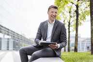 Happy businessman with tablet sitting outside in the city - DIGF06842