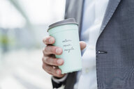 Close-up of businessman holding recycable takeaway coffee cup - DIGF06854
