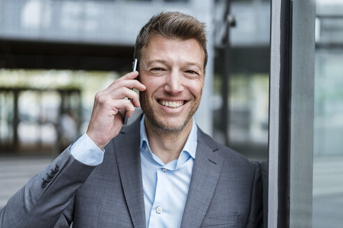 Portrait of happy businessman on cell phone outdoors - DIGF06890