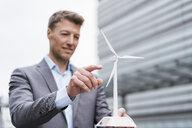 Businessman with wind turbine model outdoors - DIGF06896