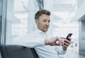 Businessman sitting in waiting area using cell phone - DIGF06917