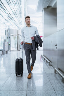 Businessman walking with baggage at the airport - DIGF06920