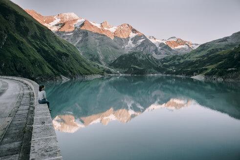 Caucasian woman sitting on wall at mountain lake - BLEF02029