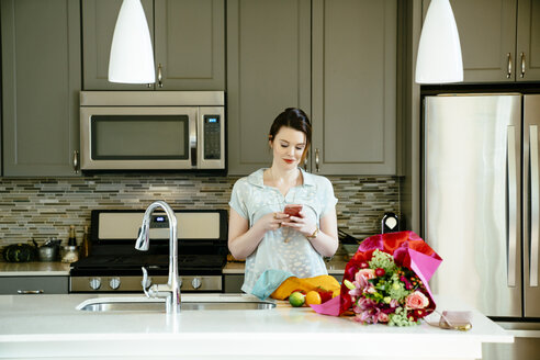 Woman texting on cell phone in domestic kitchen - BLEF02065
