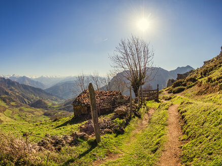 Spain, Asturia, Collada de Pelugano, ston hut at hiking trail against the sun - LAF02275