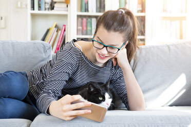Smiling girl lying on couch at home taking selfie with cat - LVF08006