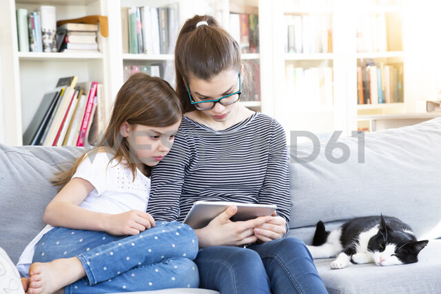 Two sisters sitting on the couch at home watching movie with digital tablet - LVF08009 - Larissa Veronesi/Westend61