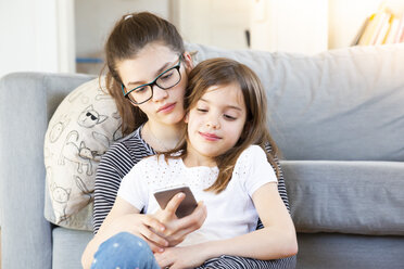 Two sisters sitting in front of couch looking at smartphone - LVF08012