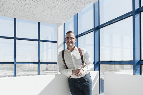 Portrait of confident businessman at the window in modern office - AHSF00211