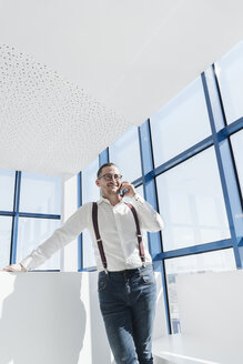 Businessman talking on cell phone at the window in modern office - AHSF00214