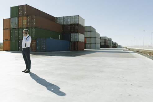 Spain, Aragon, Zaragoza, manager in logistic center near to containers with goods speaking by phone - AHSF00217