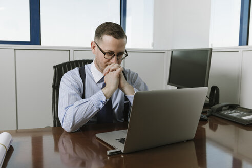 Businessman using laptop at desk in office - AHSF00226