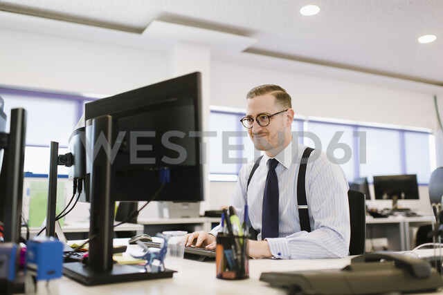 Businessman using computer at desk in office - AHSF00229 - Hernandez and Sorokina/Westend61