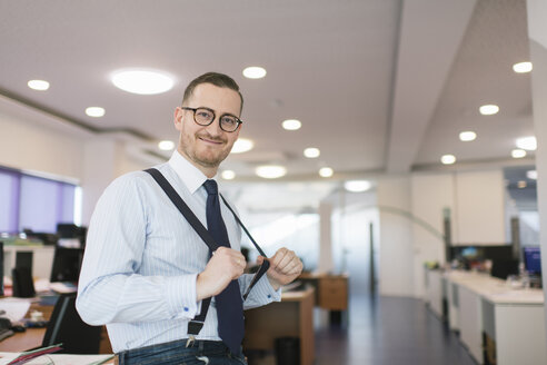 Portrait of confident businessman posing with suspenders at the office - AHSF00238