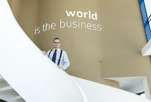 Portrait of confident businessman on stairs in modern office - AHSF00244