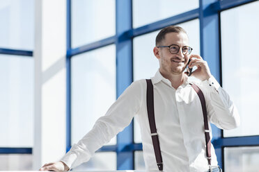 Smiling businessman talking on cell phone at the window in modern office - AHSF00262