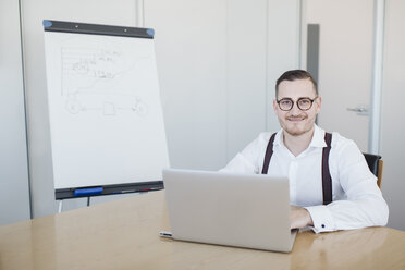 Portrait of confident businessman using laptop in conference room in office - AHSF00268