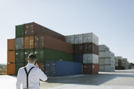Rear view of manager talking on cell phone in front of cargo containers on industrial site - AHSF00274