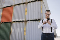 Manager in front of cargo containers on industrial site using cell phone - AHSF00283