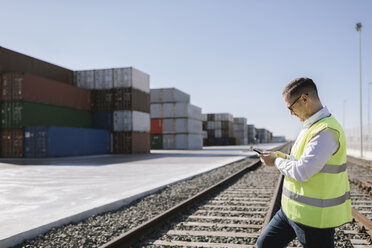 Man on railway tracks in front of cargo containers using cell phone - AHSF00286