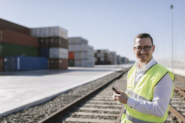 Portrait of smiling man on railway tracks in front of cargo containers with cell phone - AHSF00289