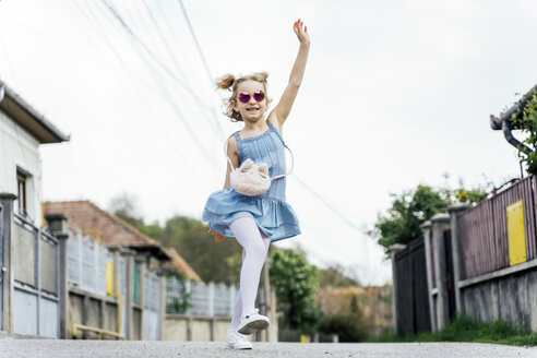 Happy little girl dancing on the street - OCMF00448