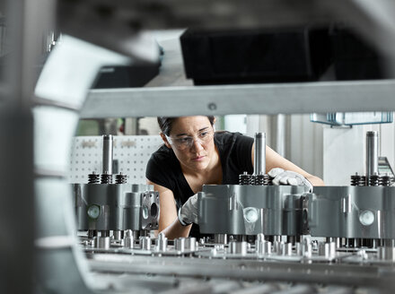 Young woman checking production line on a conveyor belt - CVF01161