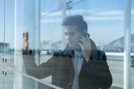 Businessman on the phone in the city behind glass pane - AFVF02830