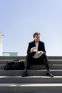 Happy businessman sitting on stairs having lunch break - AFVF02836