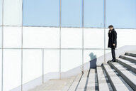 Businessman on cell phone on stairs in the city - AFVF02857