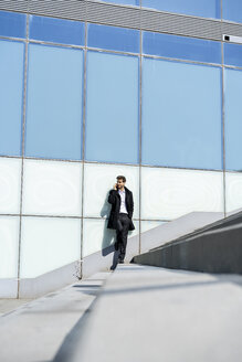 Businessman on cell phone on stairs in the city - AFVF02860