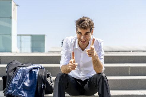 Portrait of happy businessman sitting on stairs having a break - AFVF02872