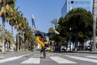 Spain, Barcelona, man in the city doing a handstand on the street - AFVF02881