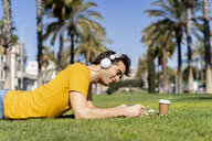 Spain, Barcelona, man lying on lawn in the city with headphones and notebook - AFVF02890