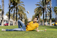 Spain, Barcelona, man lying on lawn in the city with headphones throwing up notebook - AFVF02893