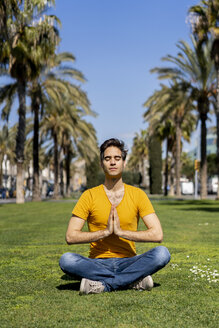 Spain, Barcelona, man practicing yoga on lawn in the city - AFVF02896