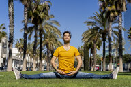 Spain, Barcelona, man practicing yoga on lawn in the city - AFVF02899