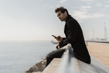 Businessman sitting on quay wall with cell phone - AFVF02902