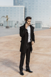 Businessman talking on cell phone in the city - AFVF02905