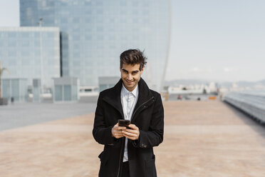 Portrait of smiling businessman holding cell phone in the city - AFVF02908
