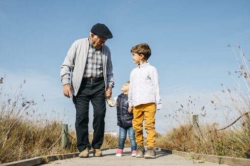 Spain, Barcelona. Grandfather with his two grandchildren strolling down a wooden walkway in the countryside. - JRFF03178