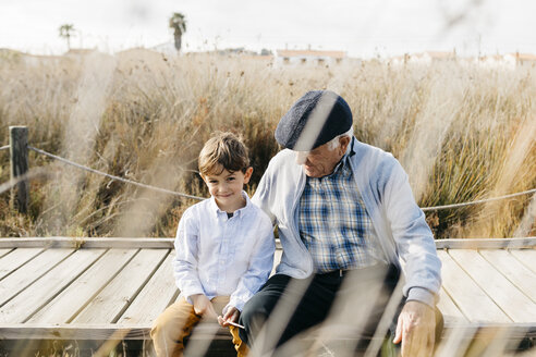 Grandfather sitting with his grandson  on boardwalk relaxing - JRFF03181
