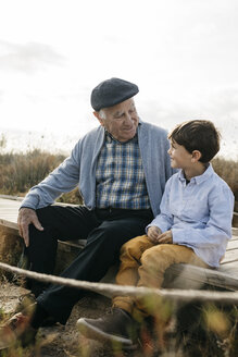 Grandfather sitting with his grandson  on boardwalk looking at each other - JRFF03184