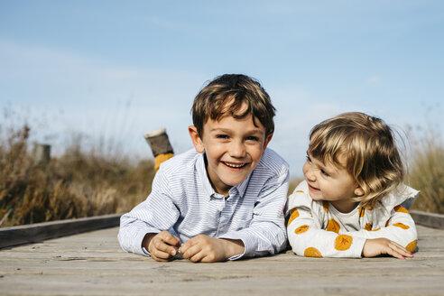 Portrait of boy and his little sister lying side by side on boardwalk having fun - JRFF03190