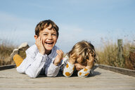 Portrait of laughing boy and his little sister lying side by side on boardwalk - JRFF03193