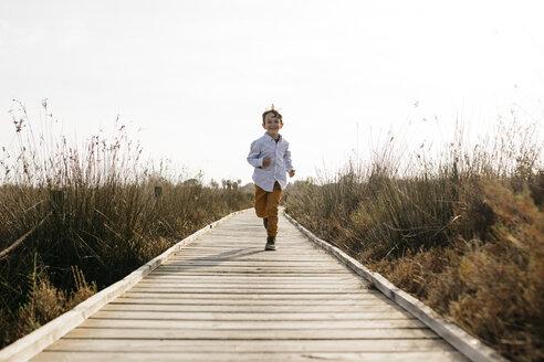 Happy little boy running on boardwalk - JRFF03199