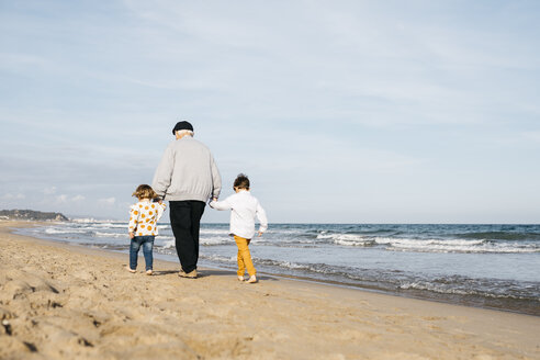Back view of grandfather strolling with his grandchildren hand in hand on the beach - JRFF03208