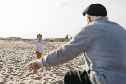 Happy little boy running into his grandfather's arms on the beach - JRFF03220