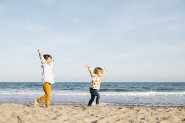 Happy boy and his little sister running together on the beach - JRFF03229