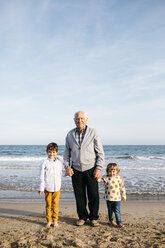 Portrait of happy grandfather standing hand in hand on the beach with his grandchildren - JRFF03232